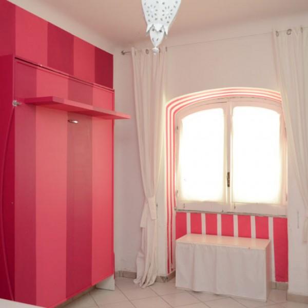 letto matrimoniale salvaspazio dipinto nello stesso colore della parete, decorata interamente a strisce