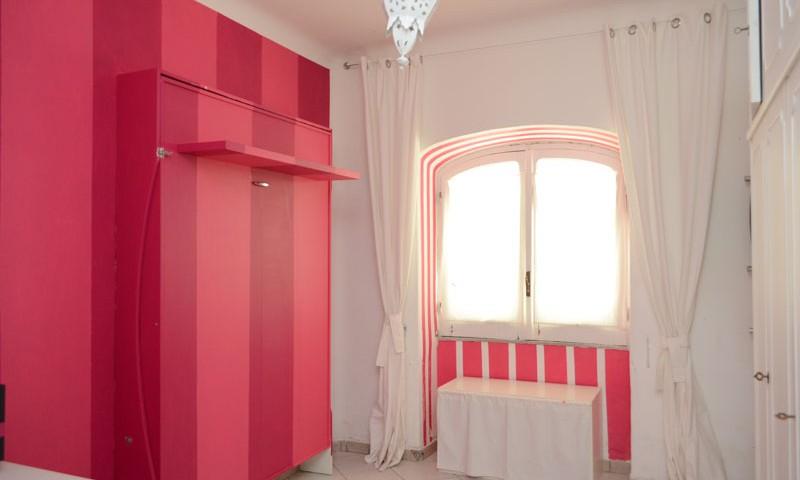 letto matrimoniale a scomparsa a parete chiuso, decorato a righe verticali dipinte su tutta la parete