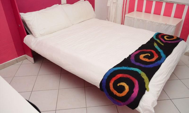 letto trasformabile matrimoniale a parete, vista del letto aperto colorato con righe in continuo sull'intera parete